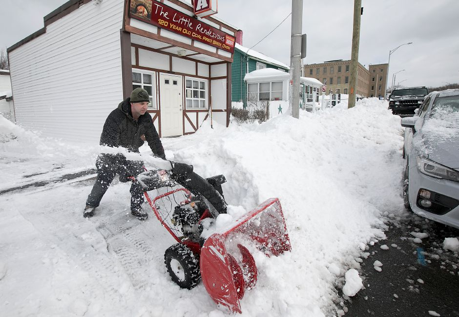 Steve Chehotsky, owner of Little Rendezvous, digs into a snow bank while preparing the popular pizza business for opening on Pratt Street in Meriden, Wednesday, March 15, 2017. | Dave Zajac, Record-Journal