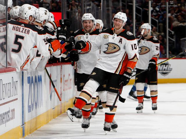 "FILE - In this March 15, 2019, file photo, Anaheim Ducks right wing Corey Perry, right, is congratulated as he passes the team box after scoring the go-ahead goal against the Colorado Avalanche during the third period of an NHL hockey game, in Denver. The Anaheim Ducks have bought out the contract of former NHL MVP Corey Perry after 14 seasons with the franchise. The Ducks announced the move Wednesday, June 19, 2019. General manager Bob Murray called it ""one of the most difficult..."