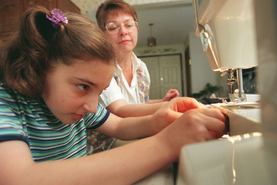 RJ file photo - Jennifer Piccolo, 12, puts her thread into the bobbin case of her sewing machine while getting sewing lessons from Jean Brennan, May 1999. Both are from Southington.