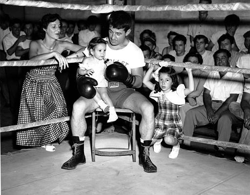New York Middleweight boxing champion Rocky Graziano takes a break from his training to feed his daughter, Roxee, as his wife, Norma, and 5-year-old daughter Audrey watch. Graziano went four rounds against two sparring partners at his camp in Summit, N.J. on Aug. 31, 1949. He is training for his Sept. 14 bout with Charlie Fusari at the Polo Grounds in N.Y. (AP Photo)