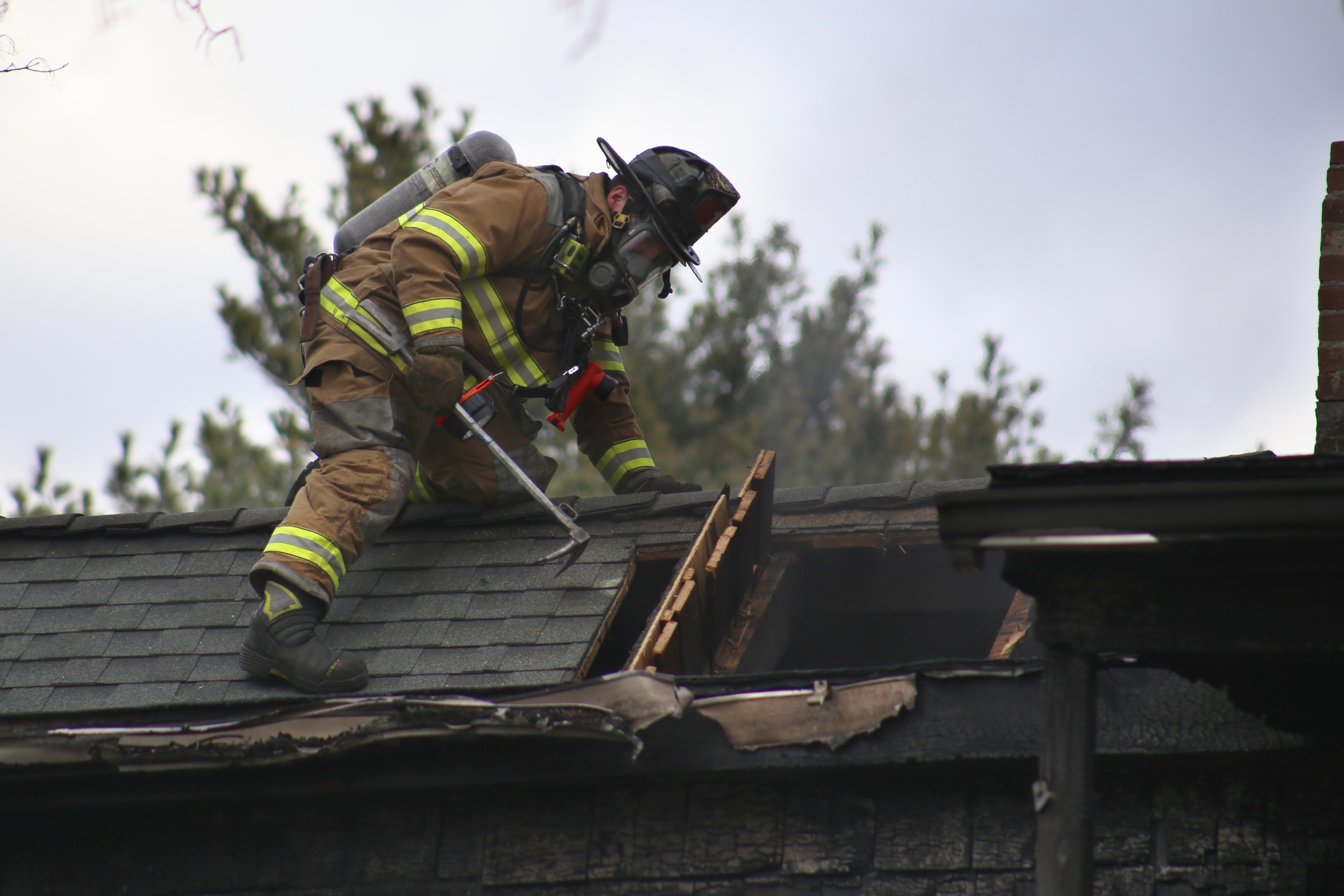 A Meriden firefighter ventilates the roof of a home at 291 Britannia St. on Dec. 1, 2014. | File photo / Record-Journal