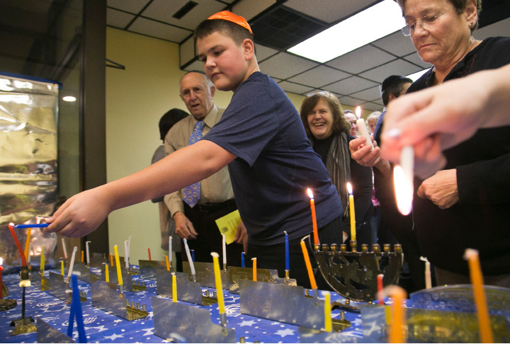 Garrett Stancuna lights a Menorah on the first night of Hanukkah in 2013.  | File photo, Record-Journal