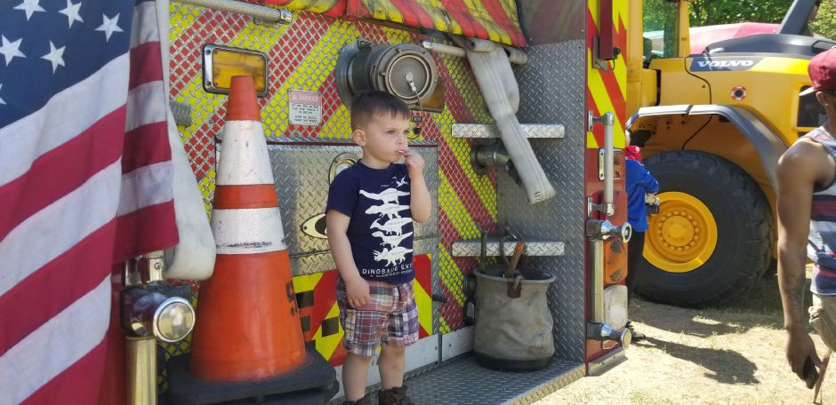 Landon Jardine, 2 of Southington, stands on the back of a Fire truck. Dozens of children and parents attended the 17th annual Touch-a-Truck event at the Southington Drive-In, at 995 Meriden-Waterbury Turnpike, on Saturday, May 18, 2019. Photos by Jeniece Roman, Record-Journal