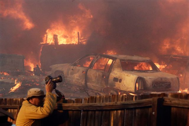 A news photographer takes pictures of a wildfire in the Lake View Terrace area of Los Angeles, Tuesday, Dec. 5, 2017. (AP Photo/Chris Carlson)