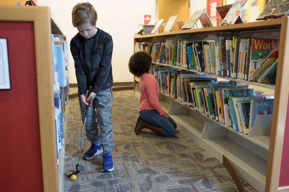 Kyle Piantek, 8, of North Haven finishes one of the holes as Kianna Grier, 8, of Wallingford finds a book. The Wallingford Public Library set up a mini-golf course on Saturday for ages 5+. Proceeds would benefit the library. Monica Jorge/Special to the Record-Journal