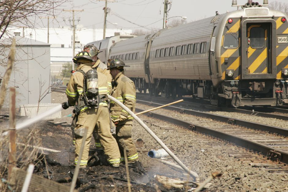 Meriden Firefighters from Engine 1 & 2 and Truck 1 battle a brush fire along the tracks at the rear of 425 and 421-419 Colony St. as a northbound train goes by Fri., March 31 around noon. A car parked in the driveway of 425 Colony sustained some fire damage to the rear.