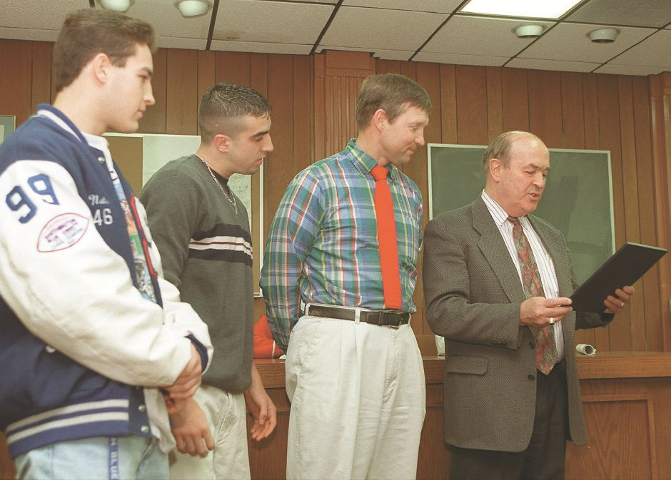 RJ file photo - Town Council Chairman Andrew Meade, right, reads a proclamation for the Southington High School football team Dec. 14, 1998 in recognition of their winning the state football championship. Next to Meade is head football coach Jude Kelly with co-captains Scott Bard and Nate Saucier.