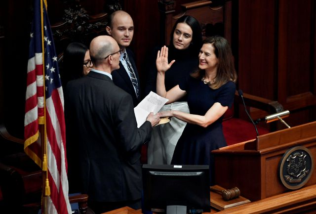 Connecticut Lt. Gov. Susan Bysiewicz, right, takes the oath of office, administered by her husband David Donaldson, left, inside the Senate Chambers at the State Capitol in Hartford, Conn., Wednesday, Jan. 9, 2019. (AP Photo/Jessica Hill)