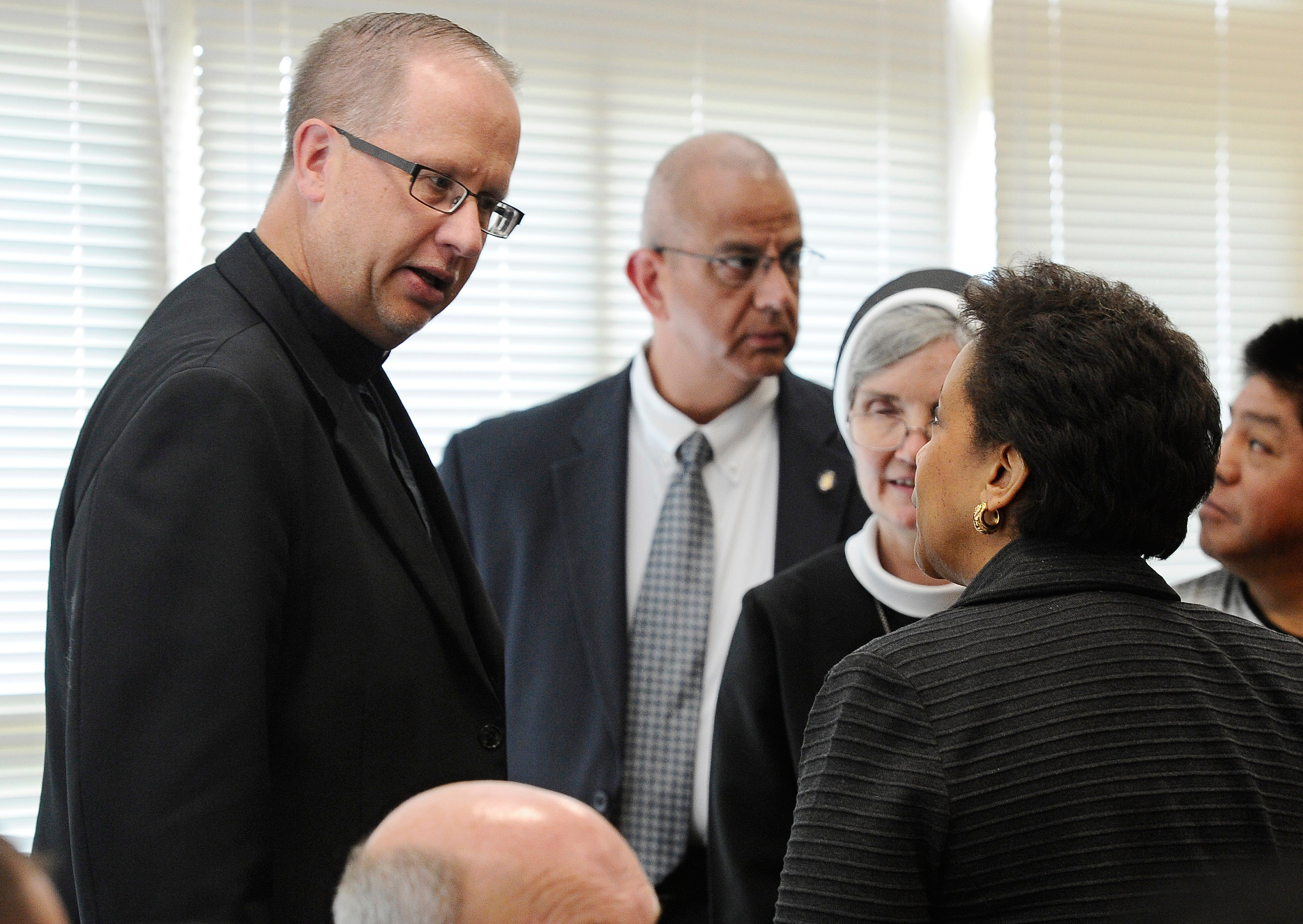 FILE PHOTO: Rev. James Manship, left, talks with  Attorney General Loretta Lynch during a community policing tour, Tuesday, July 21, 2015, in East Haven, Conn. Manship has taken over as pastor of St. Rose of Lima Church in Meriden where he says immigrants fear deportation. (AP Photo/Jessica Hill)