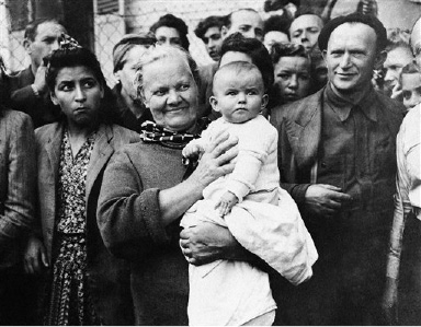 A Polish baby born in a German internment camp in the Vittel in the Vosges Mountains of France is held by its grandmother on Sept. 21, 1944, as others of the 1,500 internees from Allied nations look on. Internees were freed on September 13 on arrival of French troops from Gen. Patton's Third Army. (AP Photo)