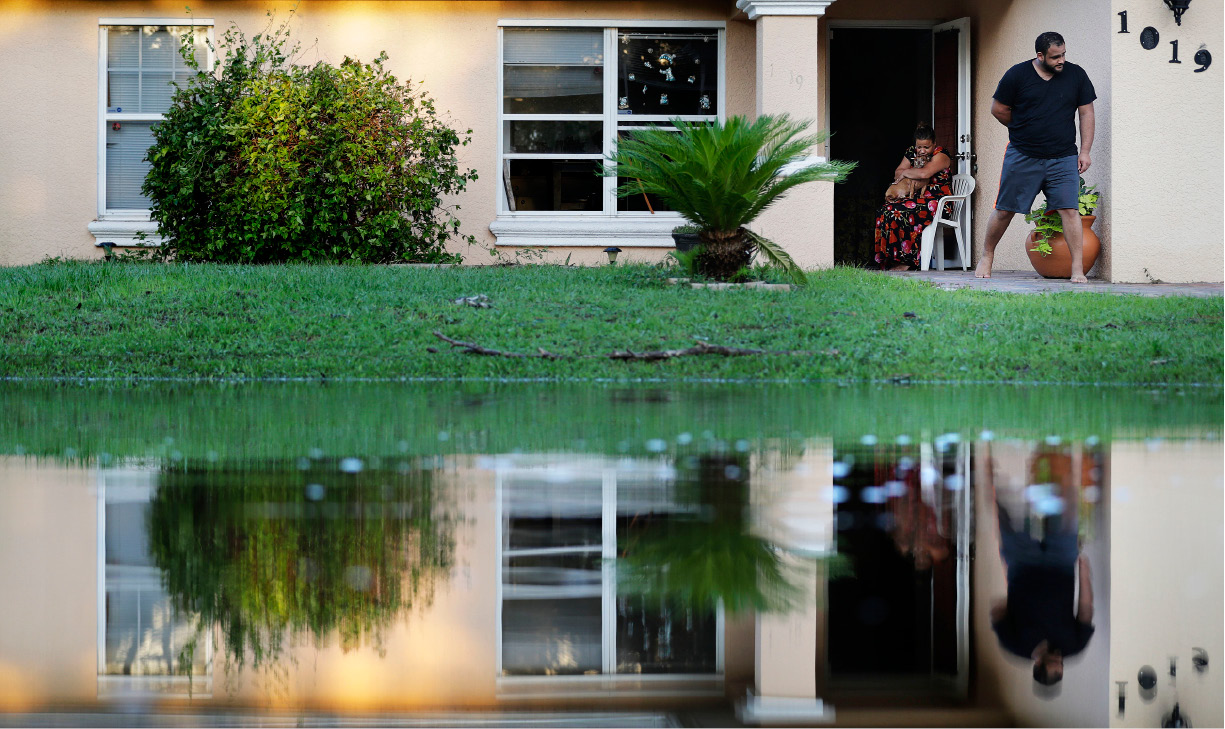"Sandra Pagan, left, escapes the heat inside her home with her dog Goldo and nephew Misael Fernandez after Hurricane Irma flooded their neighborhood leaving them without power and impassable with their cars in Fort Myers, Fla., Tuesday, Sept. 12, 2017. ""It"