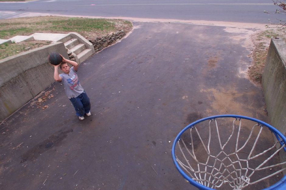RJ file photo - Philip Pender, 14, of Wallingford, enjoys the warm weather by shooting hoops in his driveway on North Elm Street in Wallingford, April 2, 1999.