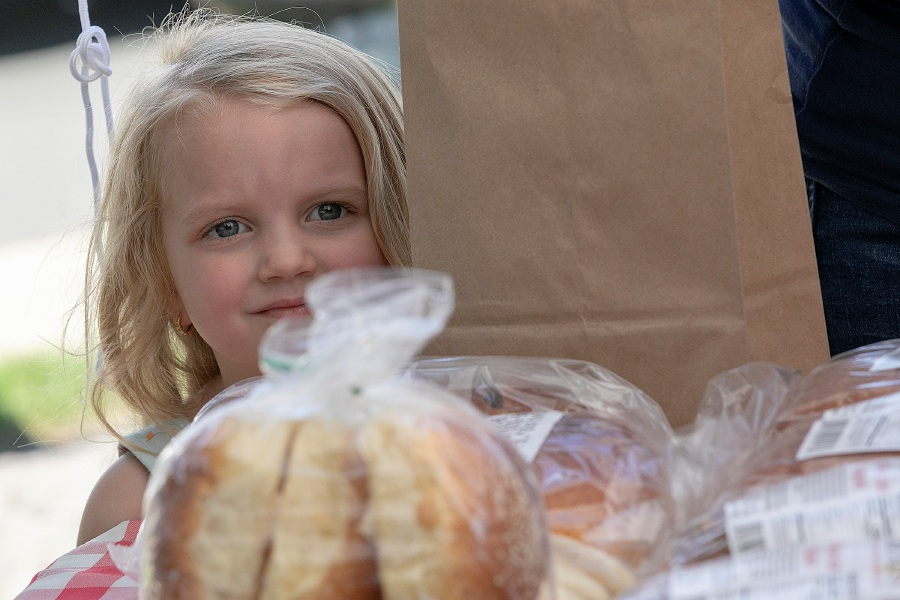 Isabella Getz, 4, of Southington eyes pastries and breads from Wave Hill Breads of Norwalk at the Farmers Market on the Southington Green on Friday.