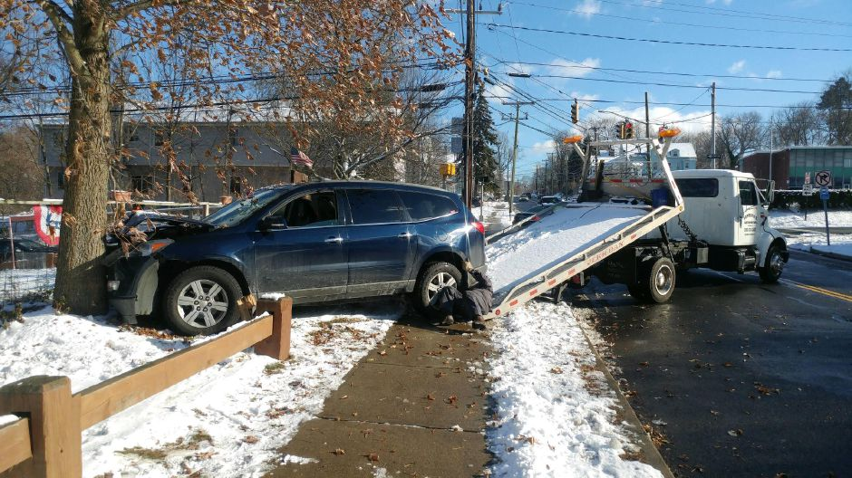 One person was taken to the hospital after a car crashed into a fence and tree on Liberty Street in Meriden on Thursday, Dec. 14, 2017. | Devin Leith-Yessian, Record-Journal