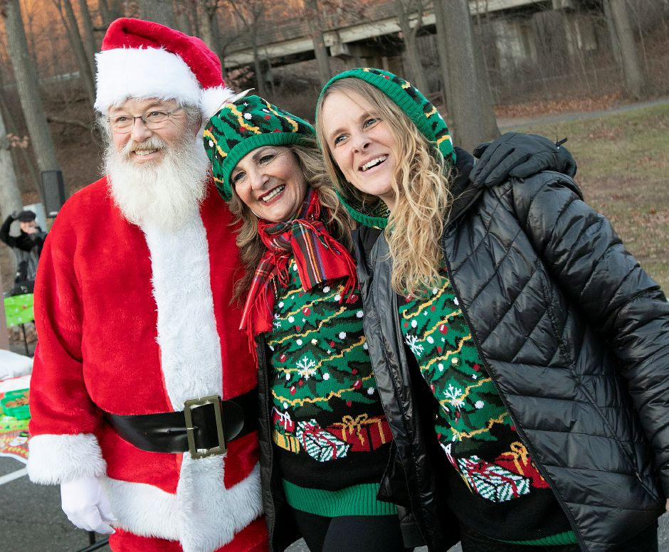 Meriden Parks and Recreation Facilities Coordinator Pamela Fuschino, center, and volunteer, Carrie Teele, of Meriden, right, pose for photos with Santa played by Bob McEvoy, of Watertown, during a Parks and Recreation Department hosted ugly holiday sweater party at Hubbard Park in Meriden Fri., Dec. 7, 2018. Dave Zajac, Record-Journal