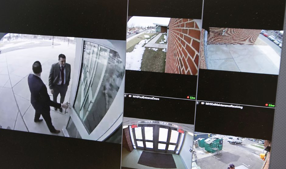 A computer monitor in the Maloney High School office shows video views of the front entrance, left, and  other school areas. around Maloney High School, Friday, March 23, 2018. City schools are using driver's license scanners to flag visitors as well as low-tech anti-shatter film on windows to deter potential intruders following the Parkland massacre and recent incidents involving adults on school grounds. Dave Zajac, Record-Journal