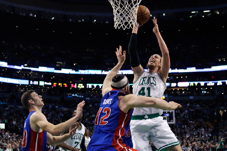 Boston Celtics center Kelly Olynyk (41) puts up a rebound over Detroit Pistons center Aron Baynes (12) during the first quarter of an NBA basketball game in Boston, Wednesday, Nov. 30, 2016. At left is Detroit Pistons forward Jon Leuer. (AP Photo/Charles Krupa)
