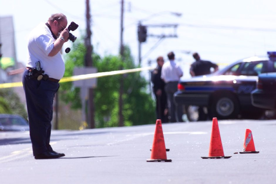 RJ file photo - Detective Mike Collins, an evidence technician with the Meriden Police Department, photographs the scene May 10, 1999 of a shooting on Lewis Avenue. The orange traffic cones mark the spot where Antonio Antolini was killed after allegedly threatening police.
