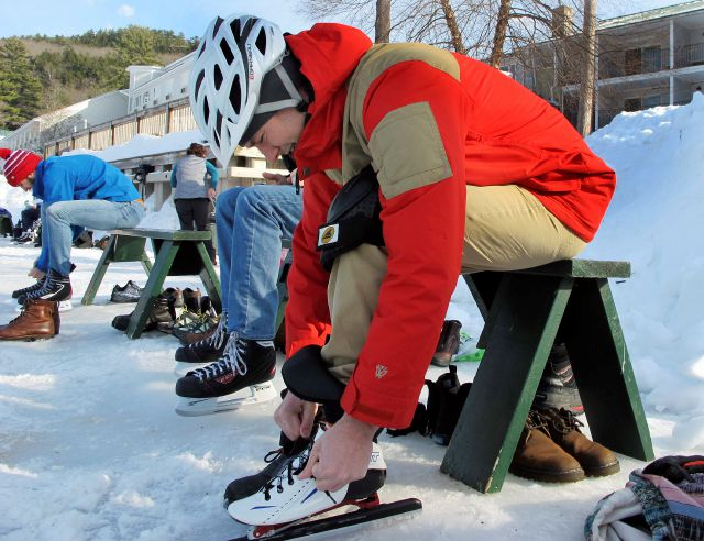 In this Jan. 20, 2018, photo, skaters put on skates in front of Lake Morey Resort in Fairlee, Vt., before heading out on the ice. The lake has a 4.5-mile Nordic skating trail that is said to be the longest in the United States. (AP Photo/Lisa Rathke)