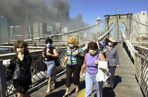 Women wearing dust masks flee across the Brooklyn Bridge from Manhattan to Brooklyn following the collapse of both World Trade Center towers Tuesday, Sept. 11, 2001 in New York. The towers previously loomed tall in the skyline behind. (AP Photo/Mark Lennihan)