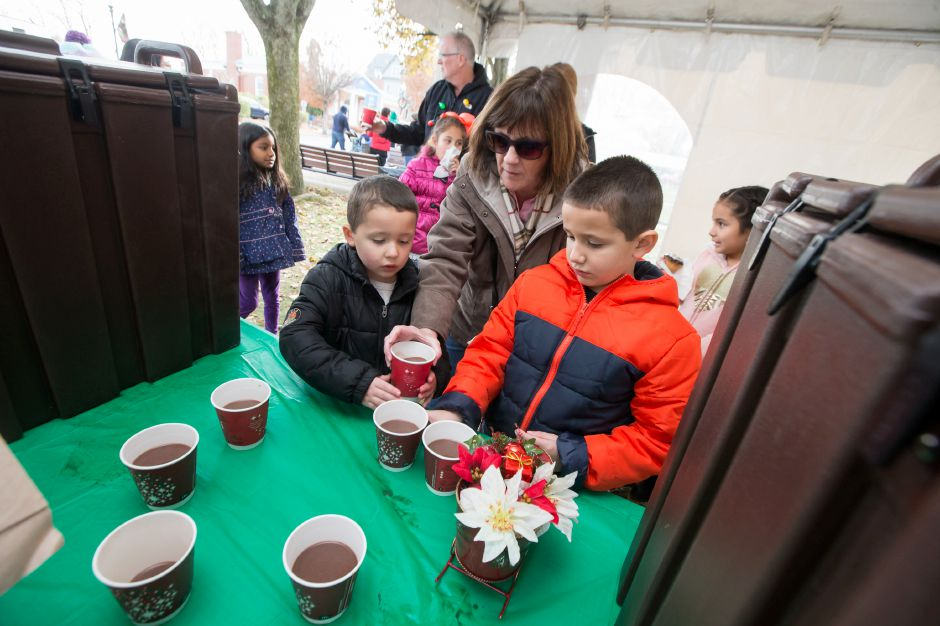 Vinny Gallo 4 left and brother Rocco 7 of Meriden pick up hot chocolate with grand ma Patricia McNamara of Wallingford Saturday during Season of Celebration at the Town Hall in Wallingford December 2, 2017 | Justin Weekes / For the Record-Journal