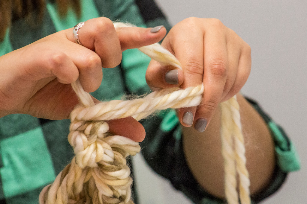 Reporter Farrah Duffany finishes her hand-made infinity scarf with one last stitch. | Richie Rathsack/Record-Journal