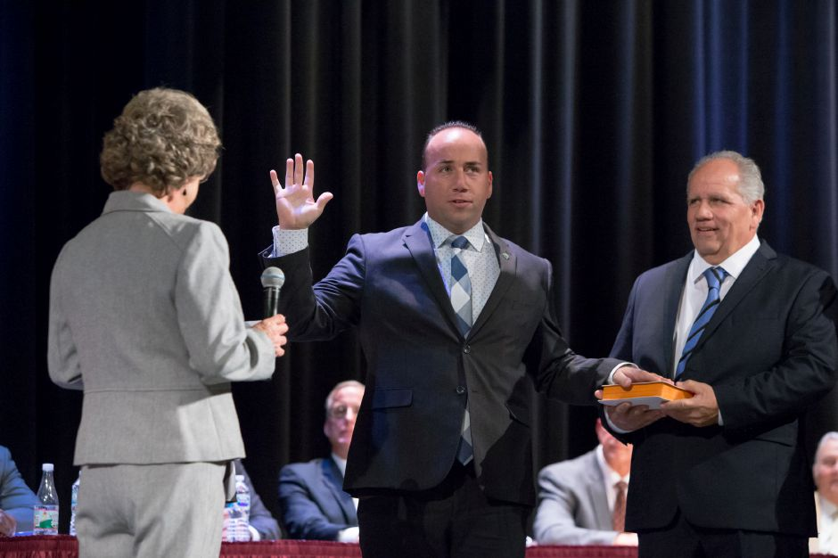 Mayor Kevin Scarpati is sworn in by City Clerk Denise Grandy left with Sal Scarpati right Monday during an Inauguration Ceremony at the Platt High School Theater in Meriden December 4, 2017 | Justin Weekes / For the Record-Journal