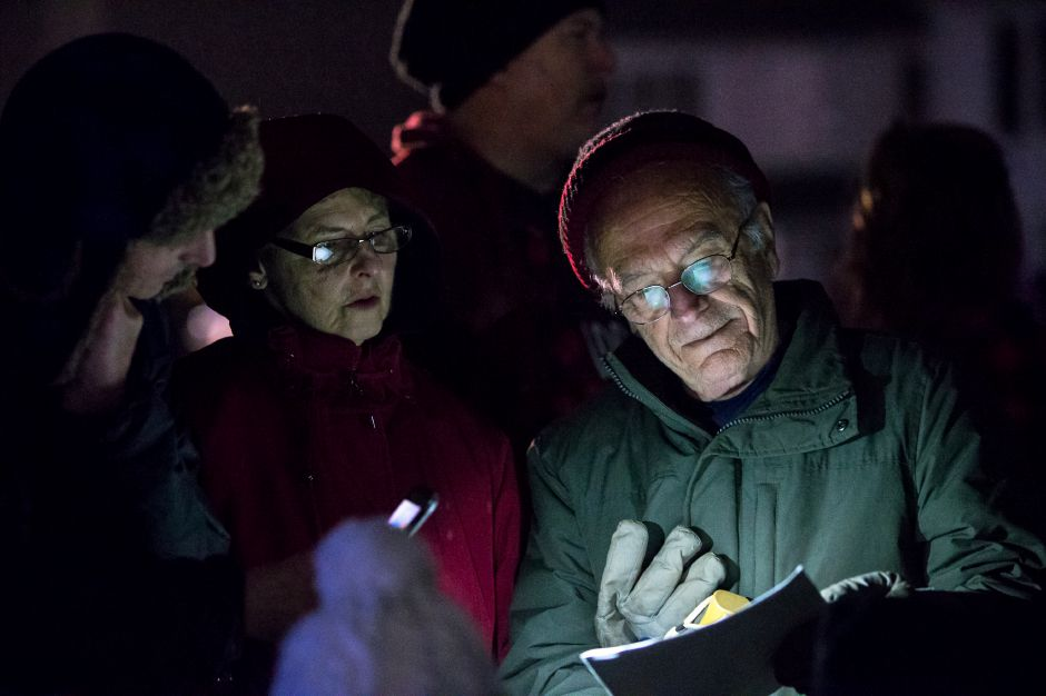 Tim Galvin left Diane and Fran Massucci read carol lyrics by flash light Sunday during the annual tree lighting at the First Congregational Church in Cheshire December 2, 2018 | Justin Weekes / Special to the Record-Journal