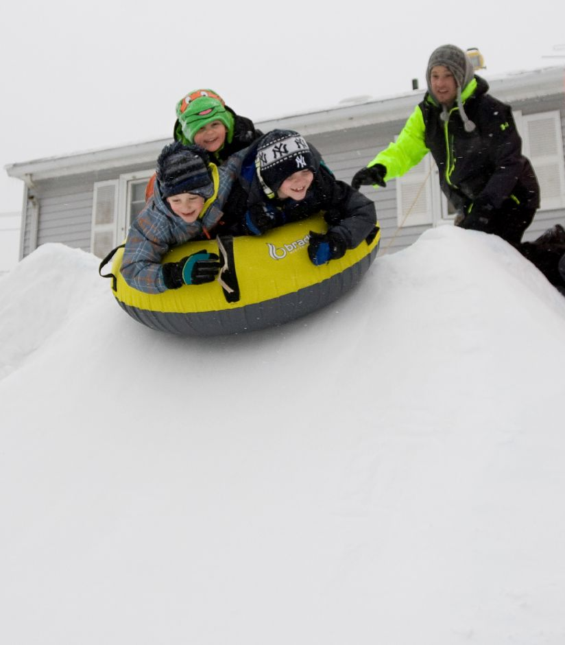 Todd Marshall, of Meriden, gives a push to sons, Mason, 4, top, Jackson, 6, left, and their neighbor, Nick Horniak, 7, down a snow chute in the backyard of the Marshall