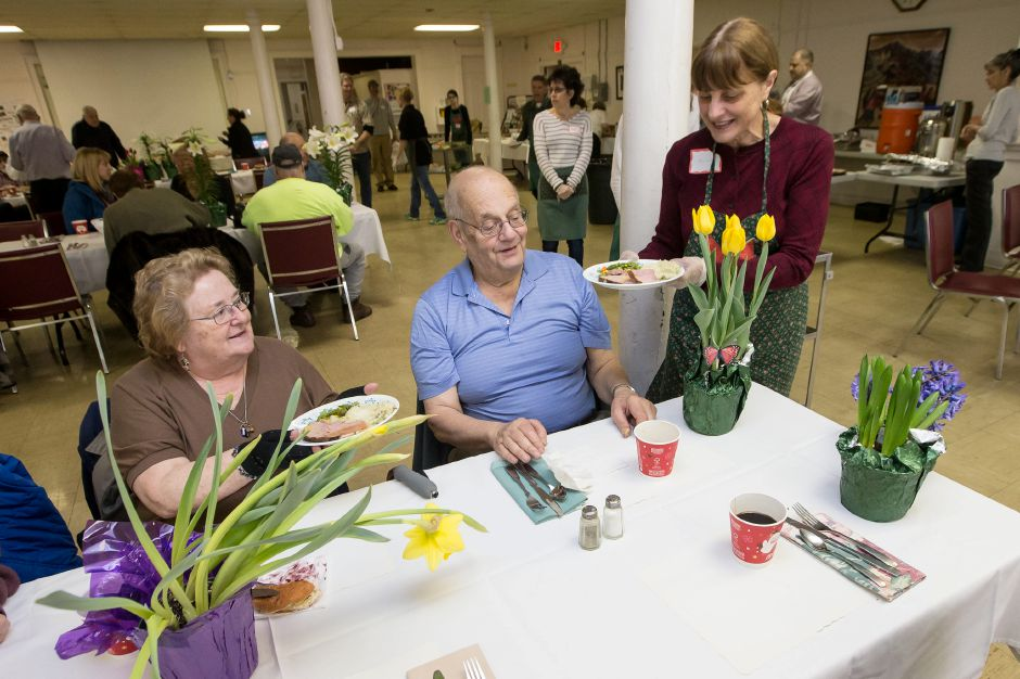Marion Miller serves a ham dinner to Linda and Ron Horozy, of Wallingford,  during the Wallingford Community Easter Dinner at the First Congregational Church in Wallingford on April 1, 2018.