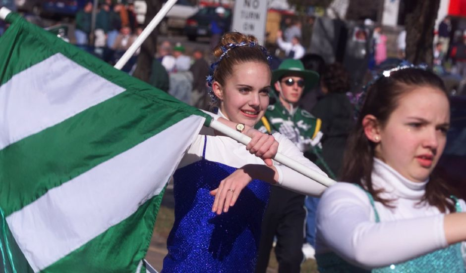 Heather Busse, left, and Alison Cole, right, march in the Maloney High School colorguard during the St. Patrick