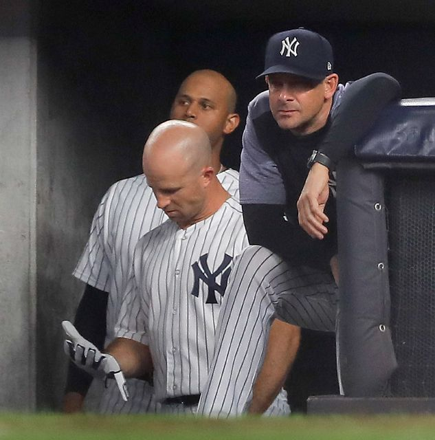 New York Yankees manager Aaron Boone watches play from the dugout during the seventh inning of Game 4 of baseball