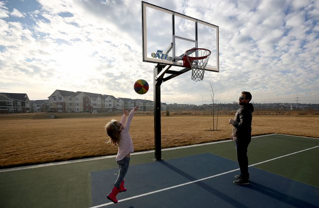 In this Jan. 5, 2018, photo, Avery Andreason, 6, plays basketball with her father, Shawn Andreason, at Bingham Junction Park in Midvale, Utah. In Utah, cities proposed potential sites and pitched their communities as potential locations for Amazon