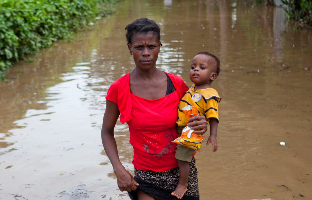 A woman carries her infant son across the flood waters of Hurricane Irma, in Fort-Liberte, Haiti, Friday Sept. 8, 2017. Irma rolled past the Dominican Republic and Haiti and battered the Turks and Caicos Islands with waves as high as 20 feet (6 meters). (AP Photo/Dieu Nalio Chery)