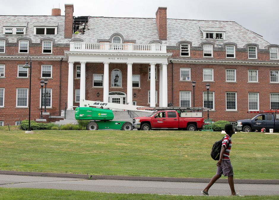 A student walks by Hill House on the Choate Rosemary Hall campus as work continues on the historic building