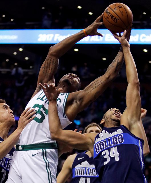 Boston Celtics guard Marcus Smart, left, grabs a rebound over Dallas Mavericks guard Devin Harris (34) during the second quarter of an NBA basketball game in Boston, Wednesday, Dec. 6, 2017. (AP Photo/Charles Krupa)