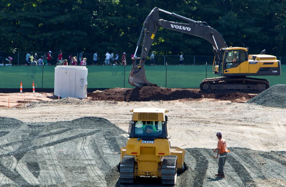 The Maloney Marching Band, in background, practices on a rear field at Maloney High School while excavation is under way for the school renovations in Meriden, Aug. 20, 2013. Construction will impact parking this year, but most student activity will go on normally while the new wing is built first. | (Christopher Zajac / Record-Journal)