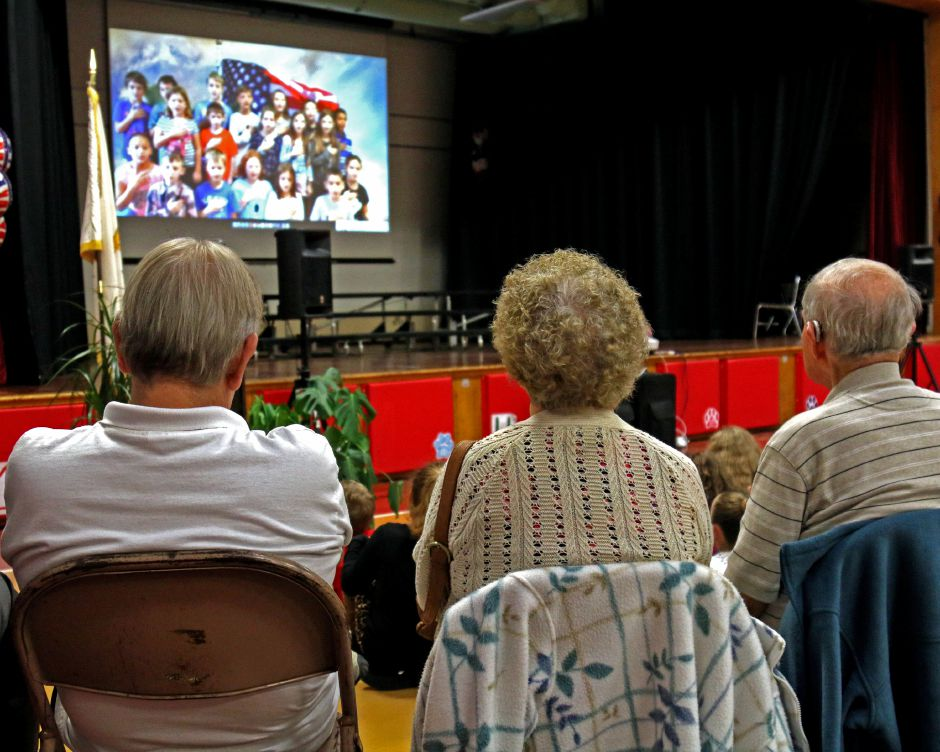 Honored guests watch a video about Veterans Day produced by third-graders. Students at Ashaway Elementary School hosted a breakfast for veterans and then performed a tribute to them in a school-wide assembly on Monday, Nov. 6, 2017. | Harold Hanka, The Westerly Sun