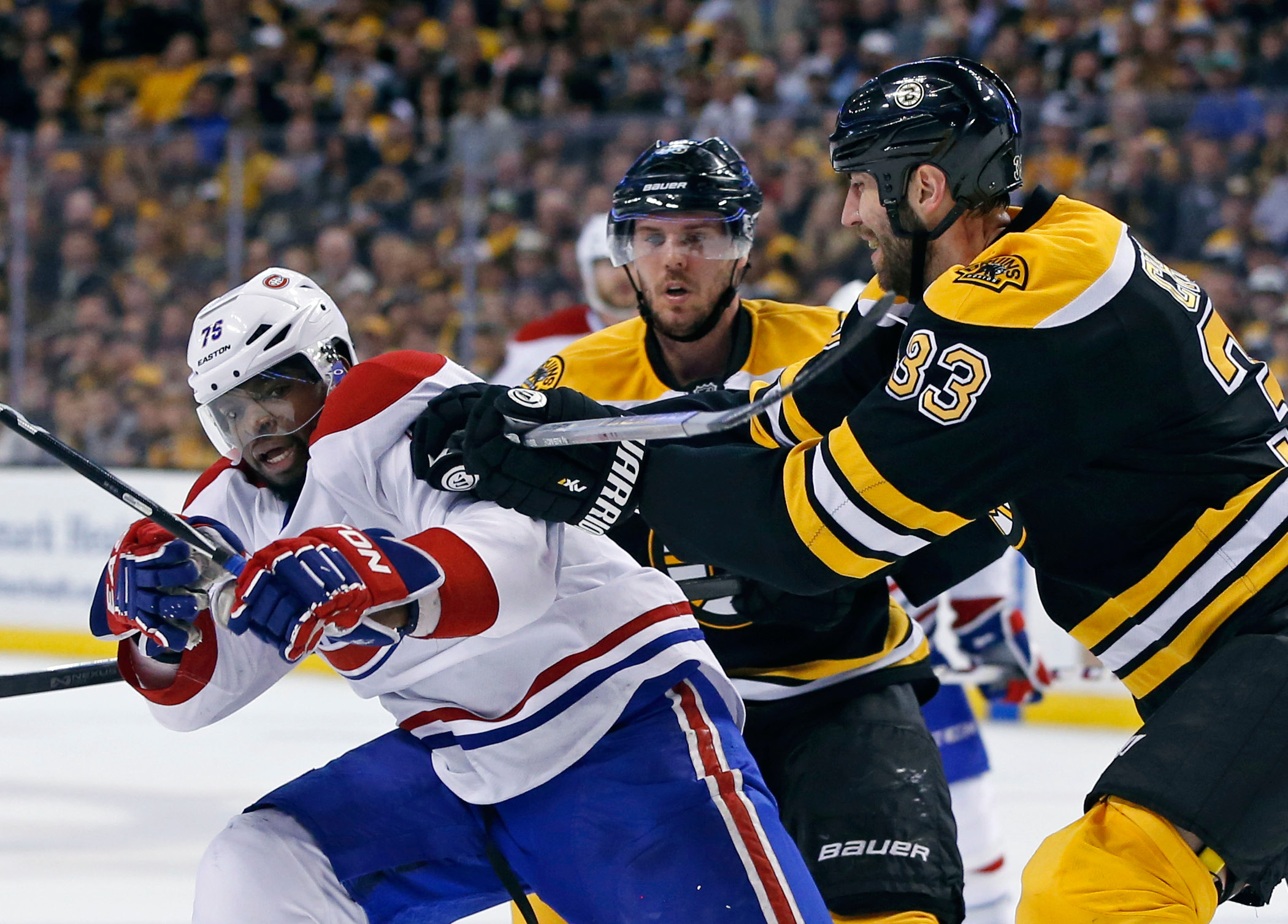 Boston Bruins defenseman Zdeno Chara (33) tries to move Montreal Canadiens defenseman P.K. Subban (76) off the puck as Bruins center David Krejci, middle, looks on during the second period in Game 2 of an NHL hockey second-round playoff series in Boston, Saturday, May 3, 2014. (AP Photo/Elise Amendola)