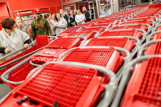 Shoppers enter and take their shopping carts during a Black Friday sale at a Target store, Friday, Nov. 23, 2018, in Newport, Ky. (AP Photo/John Minchillo)