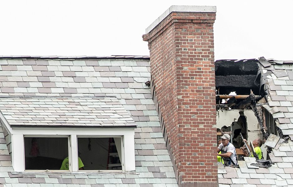 Crews from Bloomfield based Eagle Rivet Roof Service Corp. work on the damaged roof of the Hill House at Choate Rosemary Hall in Wallingford after Monday
