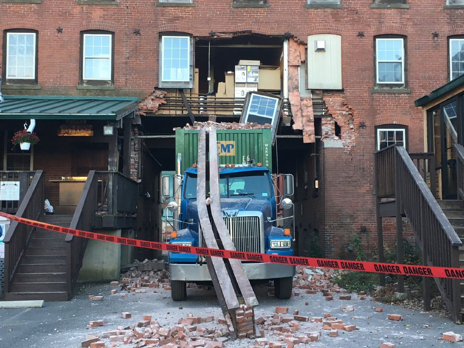 A tractor-trailer struck and damaged a West Main Street building Tuesday afternoon after it couldn't fit through an underpass. | Ryan Chichester, Record-Journal