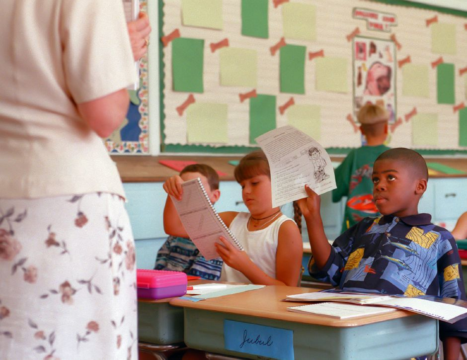 RJ file photo - Jubul Walcott, right, of Hartford, holds up a reading worksheet during a lesson on the first day of school at Derynoski School in Southington Sept. 2, 1998. Seated next to Jubul, who is one of six Choice Program pupils at teh school, is Kelsey Mazzocco of Southington.