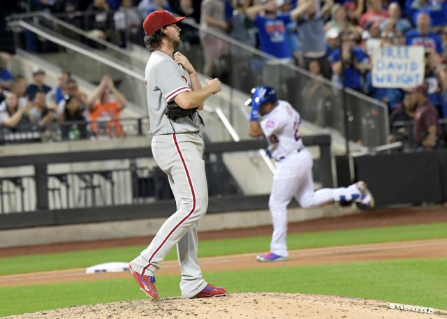 Philadelphia Phillies pitcher Aaron Nola, left, reacts as New York Mets