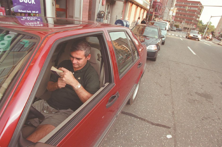 Keith Dalen, of Katonah, NY, reads in his car on Trumbull Street in Hartford while his daughter, Amy Dalen, and her friend Crystal joined other young girls at the Civic Center in Hartford for the Hanson concert, Sept. 1998.