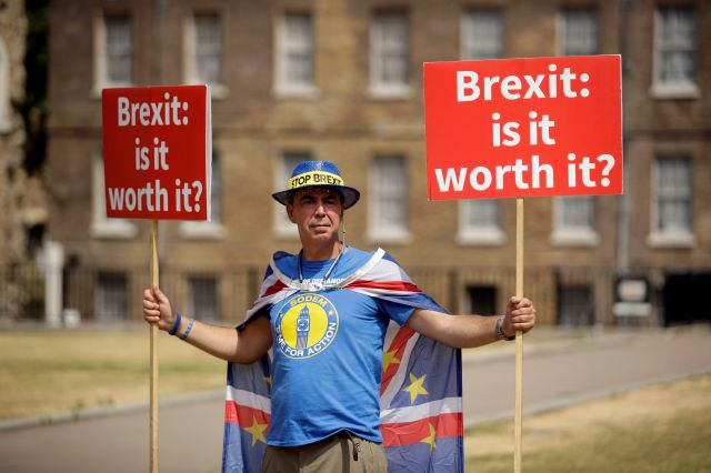 Anti-Brexit, pro-EU supporter Steve Bray holds placards on Abingdon Green across the road from the Houses of Parliament in London, Monday, July 9, 2018. Former U.K. Brexit Secretary David Davis said Monday that he won