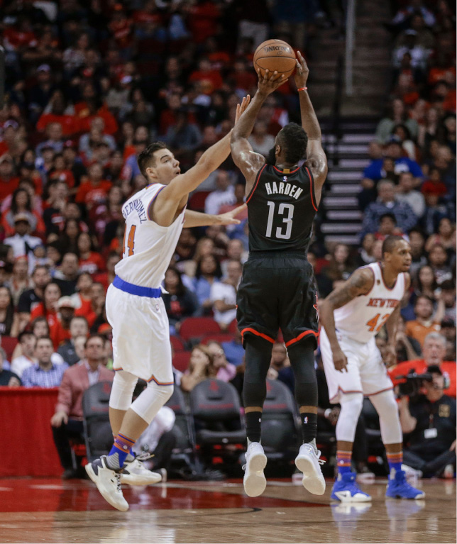 Houston Rockets guard James Harden (13) shoots over New York Knicks center Willy Hernangomez (14) during the first half of an NBA basketball game Saturday, Dec. 31, 2016, in Houston. (AP Photo/Bob Levey)