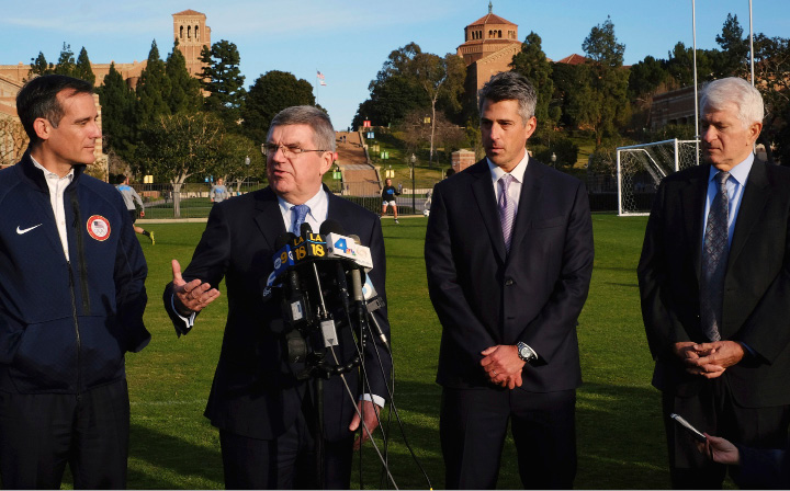 FILE - In this Feb. 1, 2016, file photo, International Olympic Committee President Thomas Bach, second from left, is flaked by Los Angeles Mayor Eric Garcetti, left, and LA 2024 chairman Casey Wasserman, second from right, and UCLA chancellor Gene Block, right, during a news conference in Los Angeles. Bach is visiting Los Angeles to check out proposed venues for the 2024 Olympic Games. The Los Angeles bid committee for the 2024 Olympics is projecting a $5.3 billion budget, a number that would be less than half the cost of the recently completed Rio de Janeiro Games and about a quarter of where Tokyo's ballooning budget for 2020 currently stands. Bid officials say they can do this because more than 30 venues already exist and those that don