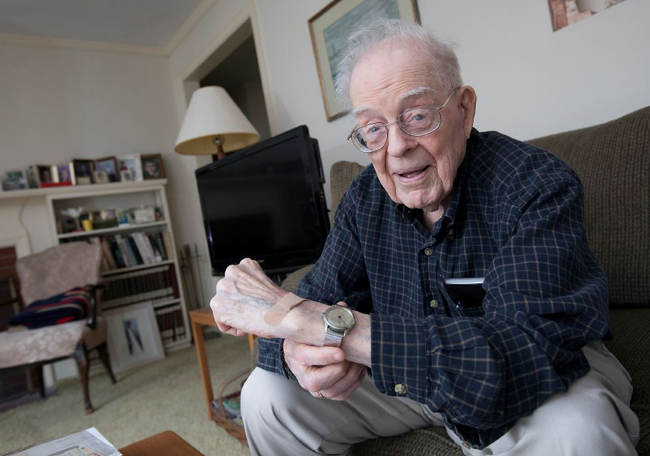 World War II Navy veteran Ralph Rowland, left, flashes a watch he bought from a ship store in Okinawa in 1945 and has worn ever since.