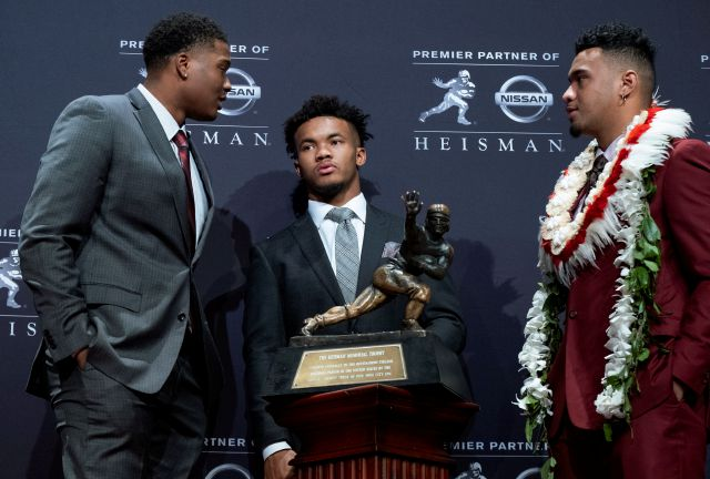 Heisman Trophy finalists, from left, Dwayne Haskins, from Ohio State; Kyler Murray, from Oklahoma; and Tua Tagovailoa, from Alabama, stand near the trophy during a media event Saturday, Dec. 8, 2018, in New York. (AP Photo/Craig Ruttle)